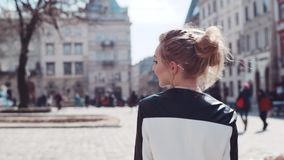 Back view of a young charming European blonde girl walking in the city, then turning to camera and sharing a bright stock video footage