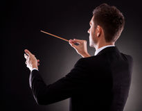 Back view of a young composer directing Royalty Free Stock Image