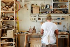 Craftsperson working. Back view of young contemporary artisan sitting by workplace on stump seat royalty free stock image