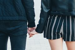 Back view of a young couple in black jackets, holding hands stock photo