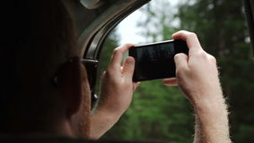 Back view of young couple driving in car and taking photos of road with smartphone.  stock video footage
