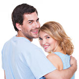 Back view of young couple in embrace. Back view of young couple in embrace standing on white background Stock Image