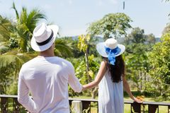 Back View Of Young Couple Holding Hands Walk To Summer Terrace Or Balcony To Look At Tropical Landscape. Back Rear View Of Young Couple Holding Hands Walk To Royalty Free Stock Image