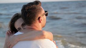 Back View of Young Couple in Love Hugging near the Sea on Waves Background. stock video footage