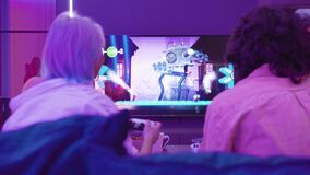 Back view of young couple play video game Sackboy Little big Planet on a Xiaomi Mi TV using PlayStation 5 gaming console