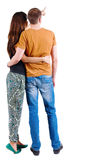 Back view of young couple pointing at wall. Royalty Free Stock Photography