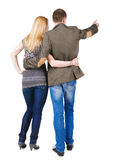 Back view of young couple pointing at wall. Royalty Free Stock Photo