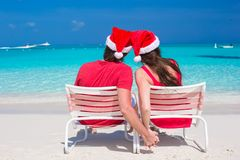 Back view of young couple in red Santa Hats. Back view of young romantic couple in red Santa hats sitting on beach and looking to each other Stock Photos