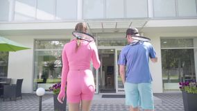 Back view of a young couple with rockets go to hotel. The girl in rose clothes and man in blue sport wear. Active stock footage