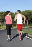 Back View Of Young Couple Running On Road stock photos
