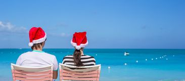 Back view of young couple in Santa hats enjoy Royalty Free Stock Image