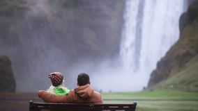Back view of young couple sitting on the bench and enjoying the beautiful view of Skogafoss waterfall in Iceland. stock video