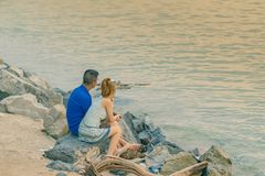 Back view of young couple sitting together on stone in front of ocean enjoying sunset royalty free stock photos