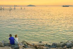 Back view of young couple sitting together on stone in front of ocean enjoying sunset stock photography
