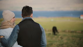 Back view of young couple standing on the field and enjoying the landscape. Man and woman look at Icelandic horses. Back view of young traveling couple standing stock video