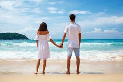 Back view of young couple standing on sandy beach Stock Photography
