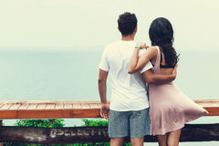 Back view of young couple standing at the top and watching seaview. Back view of young couple standing at the top, hugging and watching seaview Stock Photo