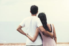 Back view of young couple standing at the top and watching seaview. Back view of young couple standing at the top, hugging and watching seaview Royalty Free Stock Photo