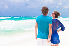 Back view of young couple on tropical beach in Stock Photos
