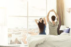 Young couple waking up in the morning in hotel room. Back view of young couple waking up in the morning, sitting on bed in hotel room stock photos