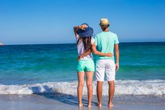 Back view of young couple walking at beach during Stock Photos