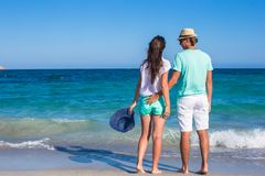 Back view of young couple walking at beach during Stock Photo