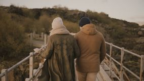 Back view of young couple walking in nature, park together. Man and woman running through the bridge and hold hands. Romantic date of traveling male and female stock video