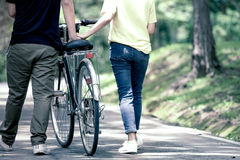 Back view of young couple walking together with bicycle royalty free stock photos