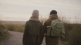 Back view of young couple walking together in national nature park. Man and woman holding hands and talking. Romantic date of male and female, family enjoying stock video