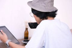 Back view. Young creative man in white shirt and padora hat sitting at table, using laptop while holding a cup of coffee royalty free stock images