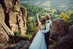 Back view of the young elegent bride showing with the hand something to the groom while standing on the top of the. Mountains. Magnificent nature view Royalty Free Stock Image