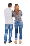 Back view of young embracing couple (man and woman) hug and look Stock Images