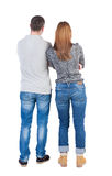 Back view of young embracing couple (man and woman) hug and look Stock Image