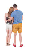 Back view of young embracing couple in shorts  hug and look. Royalty Free Stock Images