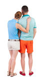 Back view of young embracing couple in shorts  hug and look. Royalty Free Stock Photo