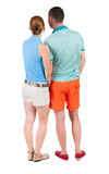 Back view of young embracing couple in shorts  hug and look. Stock Photography