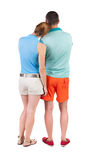 Back view of young embracing couple in shorts  hug and look. Royalty Free Stock Photography