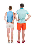 Back view of young embracing couple in shorts  hug and look. Stock Image