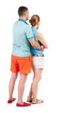 Back view of young embracing couple in shorts  hug and look. Royalty Free Stock Photos