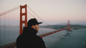 Back view young excited American man in casual clothes takes smartphone photo of sunset Golden Gate Bridge, California. stock video