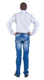 Back view of young expert looks ahead. Royalty Free Stock Photo