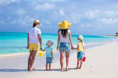 Back view young family of four on tropical beach Royalty Free Stock Images