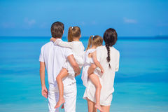 Back view of young family of four on white beach Stock Photos