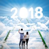 Family with number 2018 and shining door. Back view of young family standing on the stairway while looking at clouds shaped number 2018 with shining door royalty free stock photo