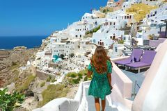 Back view of young fashion woman with green dress walking on stairs in Oia, Santorini. Female travel tourist on her summer stock image