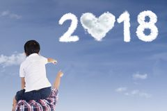 Father and child pointing at numbers 2018 Stock Photos