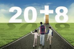 Father and children walking toward a door. Back view of a young father and his children walking toward a door with number 2018 and a Cross symbol. Shot at road Stock Photos