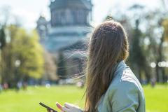 Back view of the young female with beautiful straight long hairs. Young woman with long hair in the park. Back view. Woman with phone in the park. Windy summer Royalty Free Stock Photos