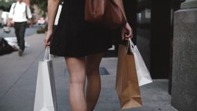 Back view of young female fashion blogger carrying shopping bags in both hands walking along the street slow motion. Successful European local girl enjoying stock video