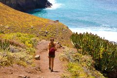 Back view young female hiker walking down to the sea on Macizo de Anaga in Tenerife stock images